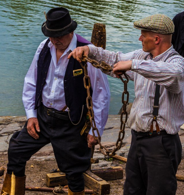 Traditionally dressed men instructing the eager public how to chain  oneself